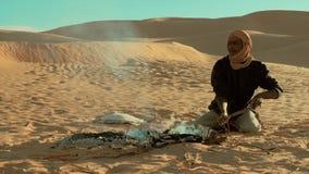 A man camping in the sahara desert. Sahara man preparing ember for bread stock video