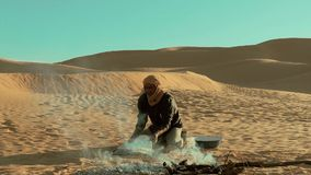 A man camping in the sahara desert. Sahara man preparing ember for bread stock footage