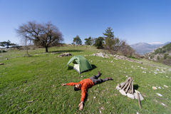 Man camping with a tent in the mountains in the summer. Stock Image