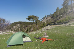 Man camping with a tent in the mountains in the summer. Royalty Free Stock Photo