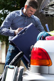 Man can't put luggage into trunk. Man can't put luggage into car trunk Stock Images