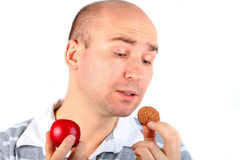 Man can't resist a cookie. Man holding a tempted cookie in one hand and a healthy fruit in the other (isolated on white Stock Images