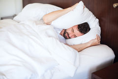 Man can't sleep due to the noise. Portrait of an attractive young man trying to sleep with a lot of noise while covering his ears with a pillow Stock Photography