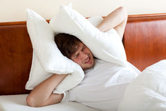 Man can't sleep because of noise. Man covering ears by pillows because of noise Royalty Free Stock Photos