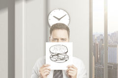 Man can't wait for lunch. Frowny businessman can't wait for lunch break, holding hamburger sketch in office interior with clock and city view. 3D Rendering Stock Image