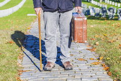 Man with cane and old suitcase in cemetery Royalty Free Stock Photo