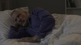 Man cannot fall sleep, exhausted by bad thoughts and sad memories, insomnia. Stock footage stock video footage