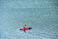 Man in canoe. Rowing on a lake mountain Royalty Free Stock Images