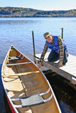 Man with canoe. Man holding canoe at dock on Lake of Two Rivers, Ontario, Canada Stock Photos