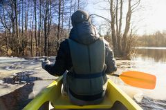 Man in canoe with paddle. Man on canoe with paddle. Sailing in flooded spring forest at Soomaa, Estonia stock photo