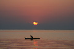 Man in a canoe at sunrise Stock Image