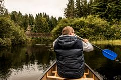 Man canoeing with Canoe on the lake of two rivers in the algonquin national park in Ontario Canada on cloudy day Stock Image