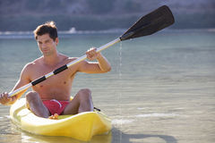 A man canoeing on a lake Stock Photography
