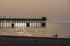 Man canoeing on the sea and Pier silhouettes at golden hour. Stock Photos