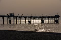 Man canoeing on the sea and Pier silhouettes at golden hour. Stock Image