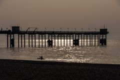 Man canoeing on the sea and Pier silhouettes at golden hour. Man canoeing on the sea and Pier silhouettes at golden hour Royalty Free Stock Photo