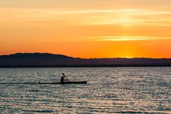 Man canoeing on sunset Stock Images