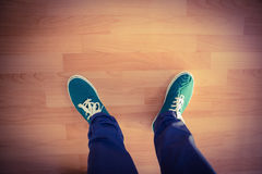 Man with canvas shoes on hardwood floor Royalty Free Stock Images