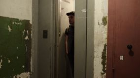 Man in cap with backpack walk out narrow elevator. Old house. Ragged walls