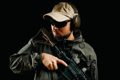 Man in cap holding assault rifle. Man in cap and jacket keeps assault rifle Stock Photography