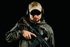 Man in cap holding assault rifle. Man in cap and jacket keeps assault rifle Royalty Free Stock Photo
