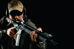 Man in cap holding assault rifle Royalty Free Stock Photos