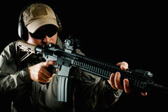 Man in cap holding assault rifle. Man in cap and jacket keeps assault rifle Royalty Free Stock Image
