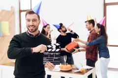The man in the cap keeps the movie clapperboard. The men in the cap keeps the movie clapperboard. His colleagues followed him. They also have hoods on their Stock Photos