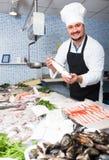 Man in cap showing fish Royalty Free Stock Photos