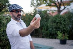 Man showing golf ball in his hands royalty free stock image