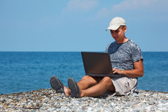 Man in cap sitting on beach with laptop on knees stock images
