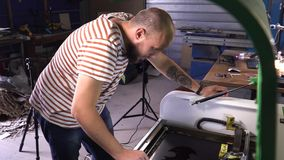 A man in striped t-shirt working on cutting wood machine. Man is bold with beard stock video