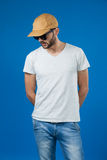 Man in cap and sunglasses. Standing against blue background Royalty Free Stock Photos