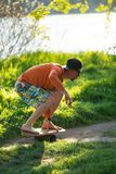 Man in cap is training on the balance board on a green meadow. Next to river on sunny evening. Back light Stock Photo