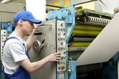 Man in cap working in newspaper factory Stock Photos