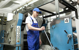 Man in cap working in newspaper factory Stock Photo