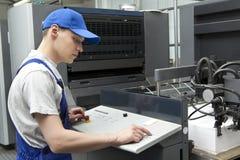 Man in cap working in print factory Stock Photos