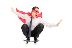Man with cape riding a small skateboard Royalty Free Stock Photography