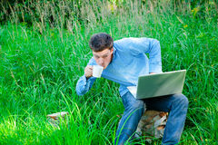 Young man outdoors with a cup and laptop Stock Image