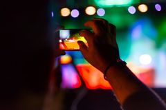 Man capturing a video on a mobile phone at a music festival. Man capturing a video on a mobile phone at a music festival Royalty Free Stock Images