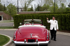 Man With Car. A sharp dressed man whistling and pointing walking next to a classic convertible car Stock Image