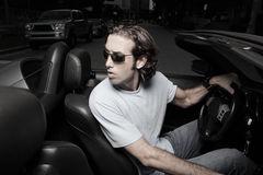 Man in a car backing up. Handsome young man backing up his sports car Stock Photography