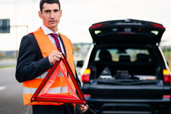 Man with car breakdown erecting warning triangle. On road Stock Photos