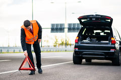 Man with car breakdown erecting warning triangle Stock Photo