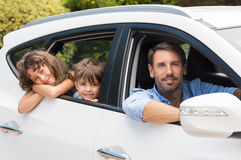 Man in car with children. Children sitting in the car looking out windows. Cute children in car going camping with father. Small young family travelling with royalty free stock photos