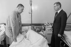 Man after car crash at hospital. KOVEL, UKRAINE - JULY 11, 2013: Vice Prime-Minister of Ukraine Oleksandr Vilkul R and man after car crash at hospital Stock Photography