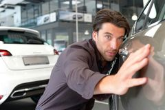 Man in the car dealership looks at a vehicle in the showroom stock photography