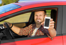 Man in car driving showing smart phone Stock Photos