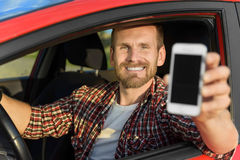 Man in car driving showing smart phone Royalty Free Stock Photography