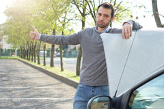 Man and car engine breakdown problem. Man hitchhiking on the road after a vehicle breakdown Royalty Free Stock Photo